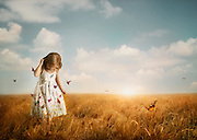 A girl in a field wearing a butterfly dress with butterflies coming alive.