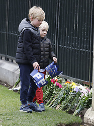 © Licensed to London News Pictures. 10/04/2021. Windsor, UK. Two boys place cardboard crowns at the Gates of Windsor Castle on The Long Walk in Berkshire. The British Royal Family have announced the death of Prince Philip, The Duke of Edinburgh, at the age of 99 today. Photo credit: Peter Macdiarmid/LNP