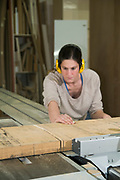 Female carpenter uses a power saw to cut oak wood