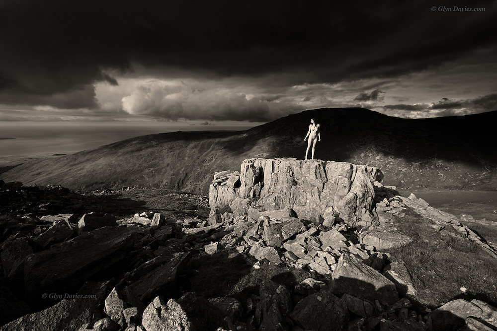 """There is a stark loneliness at this far-flung crag even in summer. The woman had been silently climbing the rocky crag to reach its flat top, where she crouched down to look around her. The slow turn of her head was the only movement in this still landscape but then she arose, her slender body illuminated by a ray of late afternoon sunshine. She turned to the light and stood on tiptoes before shouting into the breeze, """"I can't believe this! I'm alone on a mountain and I am completely NAKED! This is AMAZING!"""" She slowly rotated on her stone platform so that she could feel the warmth over every inch of her body and she revelled in the sensual experience of sun-warmed air flowing over her womanhood. She felt natural; she felt the rock; she loved the liberation and the open space. She was at one with the mountains."""