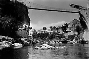 "The temporary suspension bridge erected to replace the Stari Mostar Bridge that had stood across the Neretva River since 1566. It wasdestroyed by systemic bombardment from Croat guns during the Croat Muslim War, when the Croats endeavored to "" cleanse"" the town of non Croats. Mostar, Bosnia and Herzegovina."