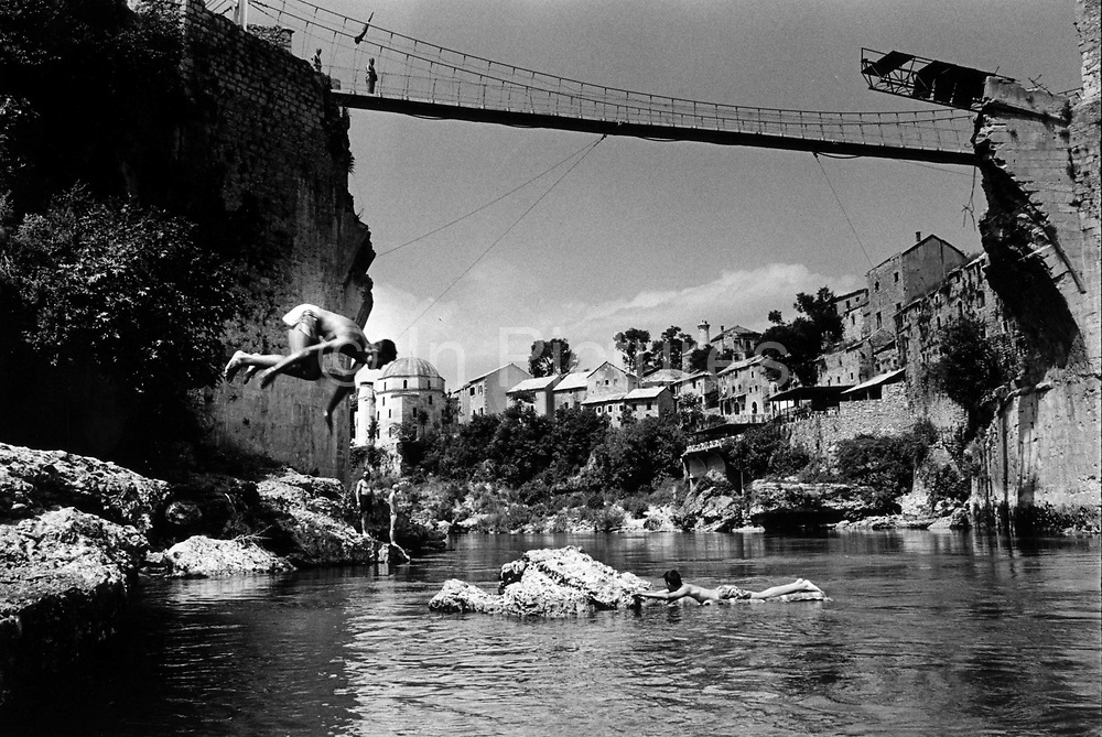 """The temporary suspension bridge erected to replace the Stari Mostar Bridge that had stood across the Neretva River since 1566. It wasdestroyed by systemic bombardment from Croat guns during the Croat Muslim War, when the Croats endeavored to """" cleanse"""" the town of non Croats. Mostar, Bosnia and Herzegovina."""