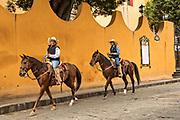 Mexican cowboys ride through the streets of San Miguel de Allende, Mexico.