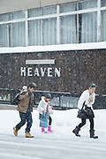 Three people walking on street in snow, Nagano, Japan