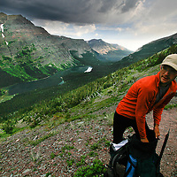 With dark clouds decending, Matt Aronson grabs another layer while climbing out of Elizabeth Lake in Glacier National Park.
