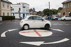 Windsor, UK. 10th July, 2021. A Fiat 500 decorated with Italian flag stripes passes a mini-roundabout painted with the St George's flag. The Royal Borough of Windsor and Maidenhead repainted several roundabouts for safety reasons previously daubed with England flags before England's Euro 2020 quarter-final match against Ukraine but it appears that local residents have restored them in advance of the Euro 2020 final between England and Italy.