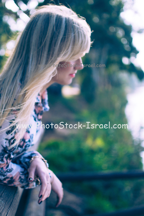 Young female blond model outdoors alone in a park