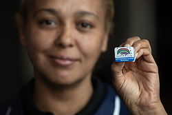 "© Licensed to London News Pictures . 22/04/2020. Manchester, UK. In an echo of Health Secretary Matt Hancock's pose with a ""CARE"" badge , Cleaner SIMONE MATTIS (43) , holds a commemorative badge , being given as a gift to those who have worked at the NHS Nightingale Hospital in Manchester . The National Health Service has built a 648 bed field hospital for the treatment of Covid-19 patients , at the historical railway station terminus which now forms the main hall of the Manchester Central Convention Centre . The facility is treating patients from across the North West of England , providing them with general medical care and oxygen therapy after discharge from Intensive Care Units . Photo credit : Joel Goodman/LNP"