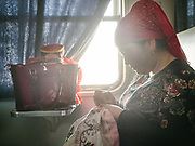 A woman sewing embroidery. Life inside the train - mostly Muslim Uighur people  ride this train.