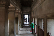 A woman sweeps her cleaning brush along the walkway within the ancient temple  of Angkor Wat Siem Reap, Cambodia.  Angkor Wat is one of UNESCO's world heritage sites. It was built in the 12th century and is Cambodia's main tourist destination. Tourists explore the site in the background.  (photo by Andrew Aitchison / In pictures via Getty Images)