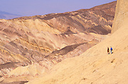 Sedimentary rock and hikers along the Zabriskie Point Trail,  Death Valley National Park, California