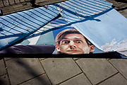 The remains of a billboard, now laying on the ground in a south London street. After heavy rain the layers of the advert are lying on the pavement next to a railing whose shadows from afternoon sunshine make strong diagonal lines across this detail. The sheets are drying out but need throwing away, a disposable facet  of this multi-media world. The face of a model looks shocked and surprised to be abandoned on the pavement like this.