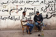 Men smoke shisha outside the small Cafe Tahrir next to the protests in front of political graffiti, Cairo, Egypt