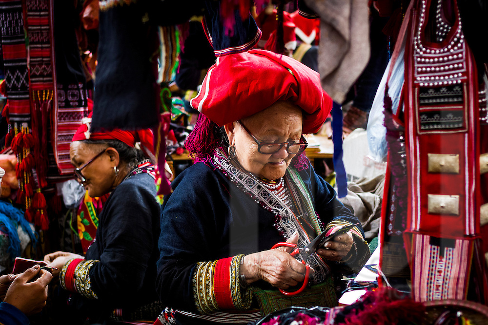 A Red Dao woman at work in a colorful market in Sapa, Lao Cai Province Vietnam, Southeast Asia