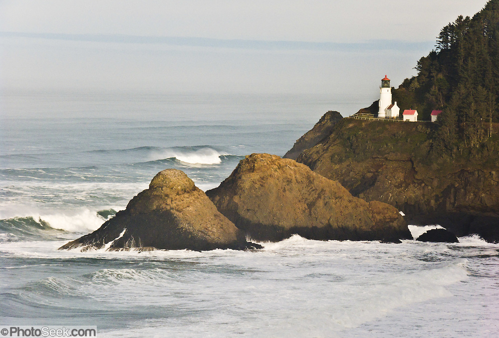 """Heceta Head Lighthouse at sunset in winter, seen from """"Lighthouse & Sealion Beach Vantage Point"""" along Highway 101 on the Oregon coast, USA. Here, the Siuslaw Indians traditionally hunted sea lions and gathered sea bird eggs from offshore rocks. While seeking to extend Spanish hegemony in the late 1700s, Spanish explorer Bruno de Heceta mapped the mouth of the Columbia River and much more along the Pacific Northwest coast; and in 1862, the US Coast Survey named Heceta Head in his honor. Built atop a 56-foot tower in 1893, this Lightstation's coastal safety beacon was first illuminated in 1894. Perched 205 feet above the ocean, its fresnel lens focuses the brightest light on the Oregon coast, visible up to 21 miles out to sea. Heceta Head is found halfway between Yachats and Florence (2.1 miles south of Carl Washburne State Park). From the large parking lot, walk 1 mile round trip to the Lighthouse. (Heceta Head Lighthouse State Scenic Viewpoint was created in the 1990s by combining Heceta Head State Park with the former Devils Elbow State Park at the scenic cove at the mouth of Cape Creek.)"""