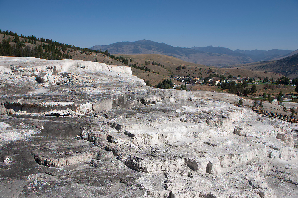 Mammoth Hot Springs, Wyoming, at the northern entrance to Yellowstone National Park. The main attraction at Mammoth Hot Springs is the terraces. Heat, water, limestone, and rock fracture combine to create the them. Travertine is deposited as white rock. The Mammoth Hot springs are constantly changing. As formations grow, water is forced to flow in different directions. The constant changes in water and mineral deposits create a living sculpture. Mammoth Hot Springs is divided into two sections, the lower terraces, and the Upper terrace Loop.