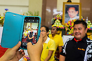09 OCTOBER 2014 - BANGKOK, THAILAND: A man has his picture taken with his smart phone in front of a portrait of Bhumibol Adulyadej, the King of Thailand in the lobby of SIriraj Hospital. The King has been hospitalized at Siriraj Hospital since Oct. 4 and underwent emergency gall bladder removal surgery Oct. 5. The King is also known as Rama IX, because he is the ninth monarch of the Chakri Dynasty. He has reigned since June 9, 1946 and is the world's longest-serving current head of state and the longest-reigning monarch in Thai history, serving for more than 68 years. He is revered by the Thai people and anytime he goes into the hospital thousands of people come to the hospital to sign get well cards.   PHOTO BY JACK KURTZ