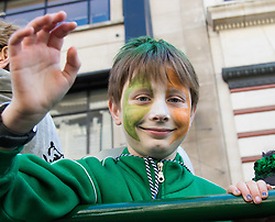 London, March 13th 2016. The annual St Patrick's Day Parade takes place in the Capital with various groups from the Irish community as well as contingents from other ethnicities taking part in a procession from Green Park to Trafalgar Square.  PICTURED: His face painted in Irish colours, a boy waves from one of the floats. ©Paul Davey<br /> FOR LICENCING CONTACT: Paul Davey +44 (0) 7966 016 296 paul@pauldaveycreative.co.uk