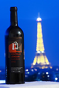 Bottle of Chapelle Lenclos against a dark blue sky background view over Paris with the Eiffel Tower illuminated Madiran France