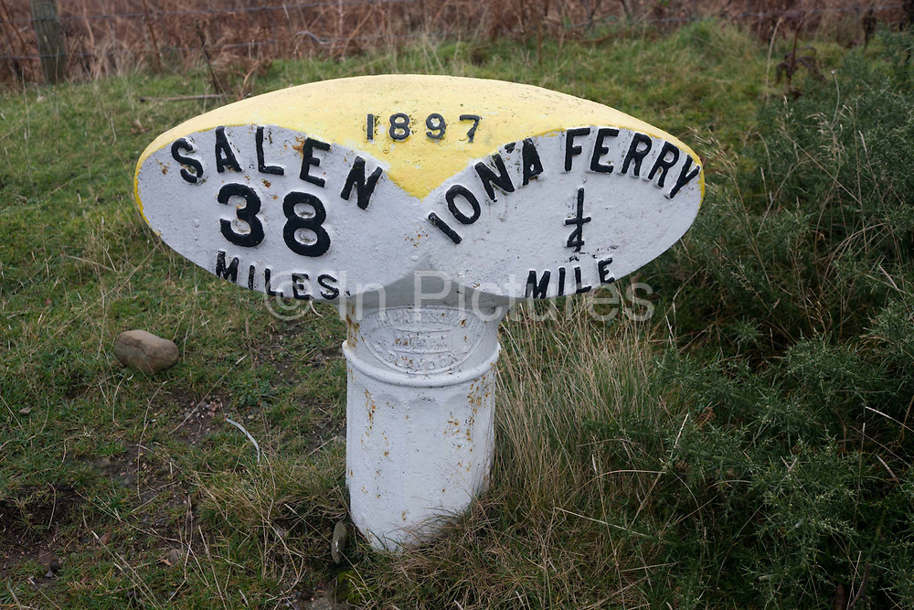 Roadside milestone between Iona ferry pier and Salen, Isle of Mull, Scotland. The Victorian era iron marker shows it was made in 1897 so has been indicating the mileage for over 110 years during which the isolation of Mull has become a tourist destination for those exploring the Inner Hebrides isles of western Scotland. It lies on the side of the A849 in the small town of Fionnphort on the Ross of Mull from where travellers cross a small sound by ferry to the Holy Isle of Iona, an stone and bronze age then Columban island settlement visited by pilgrims all over the world.
