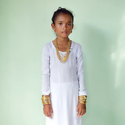 Portrait of a Muslim Cham girl wearing a white dress and bronze and copper jewellery at her Karoh (maturity) ceremony in Van Lam, Ninh Thuan province, Central Vietnam. Cham girls usually in groups of around 5, undergo a Karoh (maturity) ceremony, one of the most important ritual events of their lives and if it has not taken place, the girl cannot marry. The Cham, a Muslim community of around 39,000 people living along the coast of Central Vietnam are one of the 54 ethnic groups recognised by the Vietnamese government.