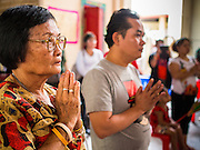 """09 AUGUST 2014 - BANGKOK, THAILAND:  People pray at the Ruby Goddess Shrine in the Dusit section of Bangkok. The seventh month of the Chinese Lunar calendar is called """"Ghost Month"""" during which ghosts and spirits, including those of the deceased ancestors, come out from the lower realm. It is common for Chinese people to make merit during the month by burning """"hell money"""" and presenting food to the ghosts. At Chinese temples in Thailand, it is also customary to give food to the poorer people in the community.         PHOTO BY JACK KURTZ"""