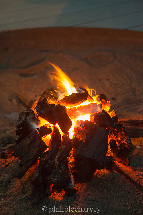 Fire burning at dusk at a Safari Lodge, Luangwa Valley, National Park, Zambia, Africa