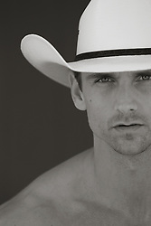 muscular shirtless cowboy against a wall