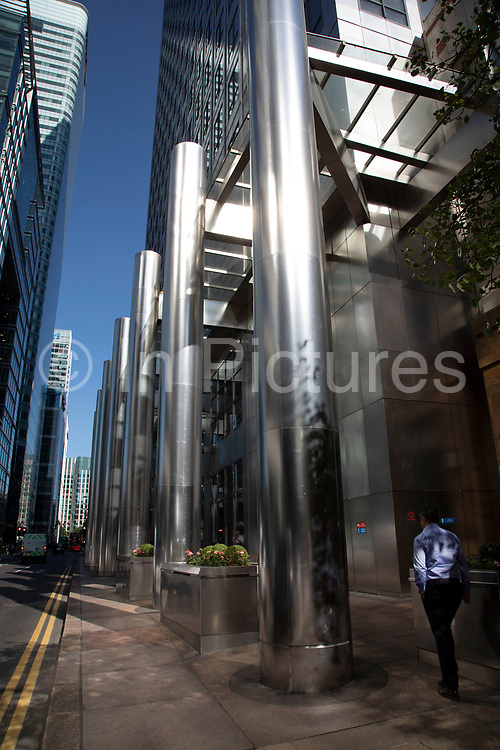 Brushed steel architectural details make for a shimmering silver view on the North Colonnade at the base of One Canada Square in Canary Wharf financial district in London, England, United Kingdom. Canary Wharf is a financial area which is still growing as construction of new skyscrapers continues.