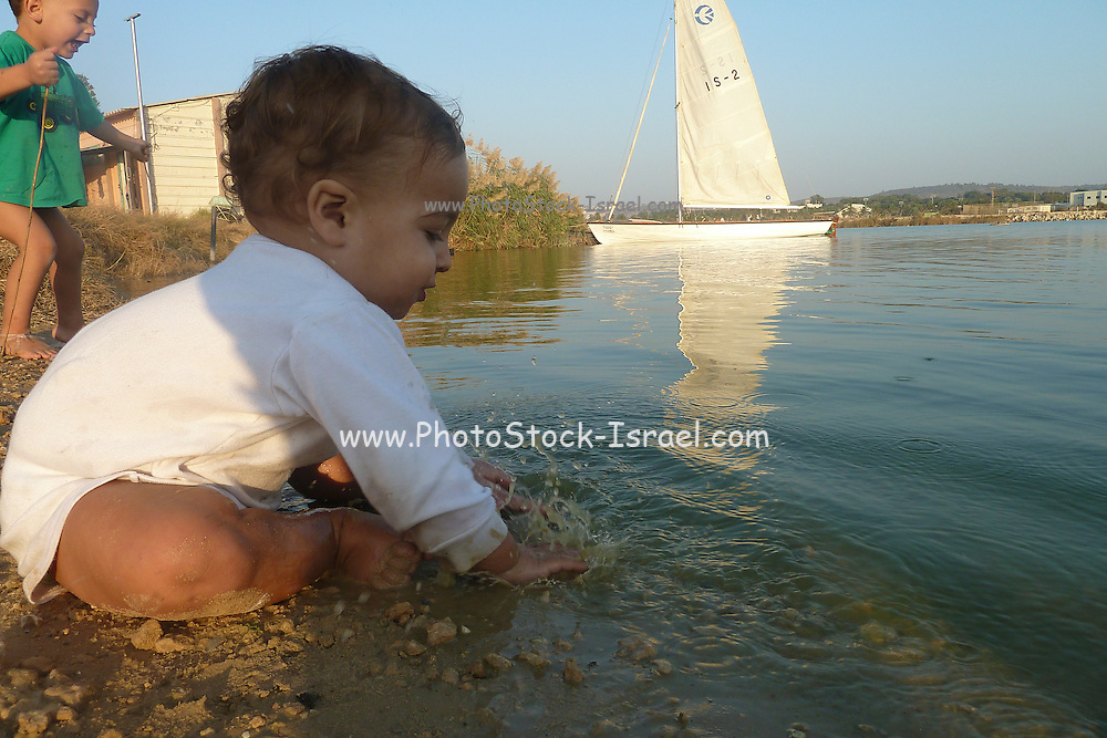 2 toddlers playing in the water of a lake. A sail boat in the background