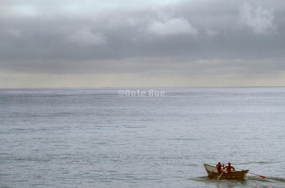 two figures rowing boat amidst vast ocean