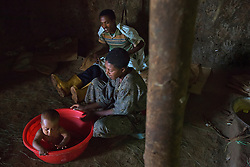 Fifteen-year-old Destaye  and her husband, Addisu, 27, bathe their son in their home near Bahir Dar, Ethiopia on Aug. 12, 2012. The couple divide their time between working in the fields and taking care of their 6-month-old baby. Like many other young couples, they tend to the domestic, economic and personal demands of being young parents. At the time of their marriage, when Destaye was age 11, she was still in school and her husband expressed interest in letting her continue her education. Since the birth of their son, however, she has had to confine her life exclusively to being a wife and mother.