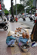 """Two women cooking and selling waffles from a """"don ganh"""" (two baskets slung from each end of a wooden or bamboo pole), on the sidewalk. Ho Chi Minh City (Saigon), Vietnam"""