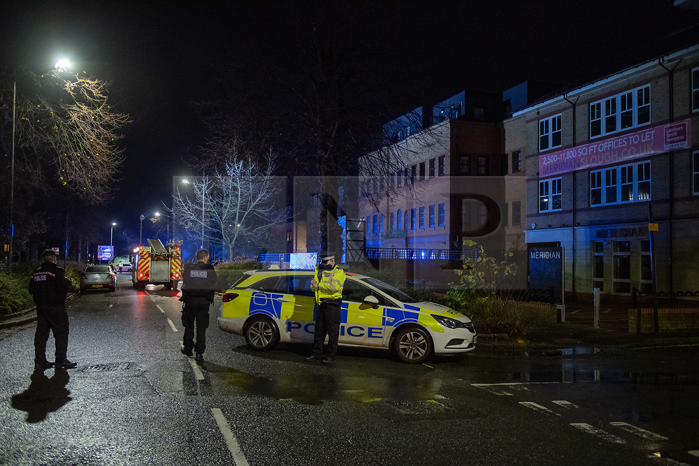 © Licensed to London News Pictures. 14/11/2020. Slough, UK. A police vehicle and fire engine parked on The Grove in Slough. A high-rise flat in Slough has been gutted by fire. Royal Berkshire Fire and Rescue Servcie and partner agencies attended the fire on Saturday evening after the fire broke out, residents of an adjacent bulding were evacuated as a precaution. Photo credit: Peter Manning/LNP