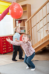Two kids playing with red balloons in kindergarten