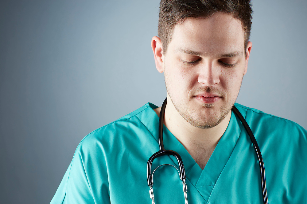 A portrait series representing the intense emotions that Doctors face.  A white male Doctor wearing a stethoscope, and green medical scrub suit shown.