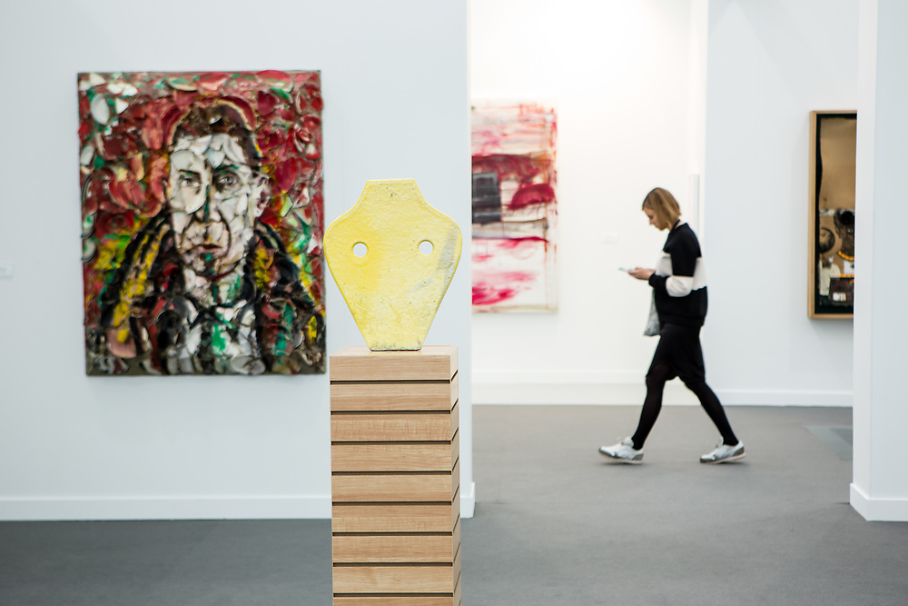 New York, NY - 5 May 2017. The opening day of the Frieze Art Fair, showcasing modern and contemporary art presented by galleries from around the world, on Randall's Island in New York City. A yellow bust mask by Pia Camil in the gallery of Blum & Poe. On the wall on the left is a portrait of Ramis Barquet by Julian Schnabel.