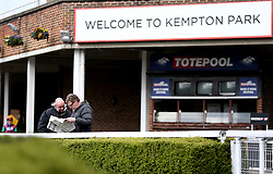 Racegoers read through racing tips in the newspaper during the Easter Family Fun Day at Kempton Park Racecourse.