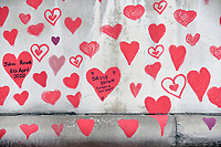 The National Covid Memorial wall along the Thames embankment<br /> decorated with red hearts by NHS volunteers <br /> each heart representing a life lost to Covid 19 during the  pandemic in the United Kingdom photo by Krisztian  Elek