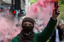 London, UK. 28th May, 2021. An activist from Palestine Action holds up a red smoke grenade during a protest outside the UK headquarters of Elbit Systems, an Israel-based company developing technologies used for military applications including drones, precision guidance, surveillance and intruder-detection systems. The pro-Palestinian activists were protesting against Elbit's presence in the UK and against British arms sales to and support for Israel.
