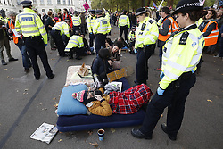 © Licensed to London News Pictures. 09/10/2019. London, UK. Extinction Rebellion activists locked together on beds are surrounded  by police at their blockade near the back entrance to Downing Street during a third day of protests in central London. The climate change group intend to blockade the Westminster area for two weeks to demand that the government takes immediate and decisive action on climate change. Photo credit: Peter Macdiarmid/LNP