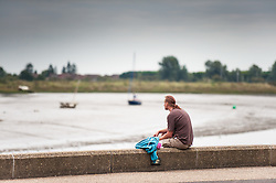 A man relaxing on the promenade at Maldon on the Blackwater River in Essex.