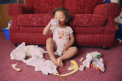 Neglected toddler sitting on floor drinking milk surrounded by dirty nappies and rubbish,