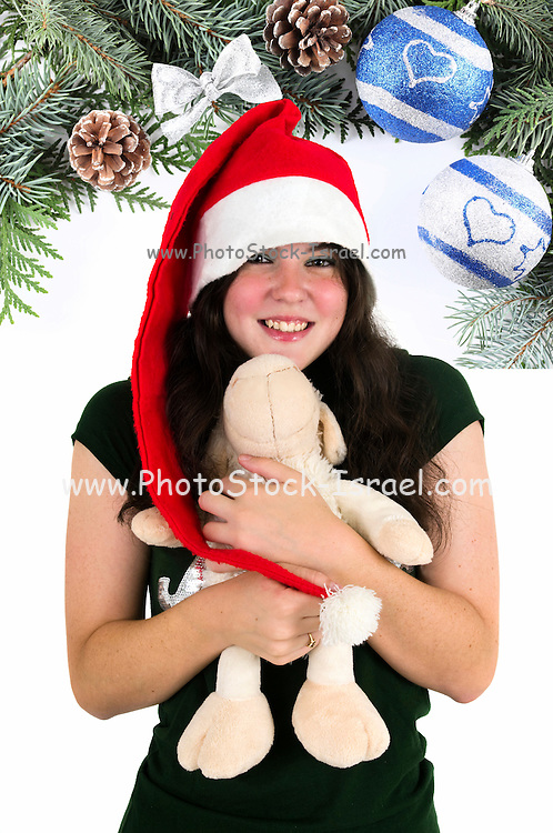 Young teen wearing Santa hat and hugs a stuffed doll and Christmas decorations in the background