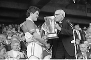 All Ireland Hurling Finals.1986..07.09.1986..09.07.1986..7th September 1986..September,every year,is the highlight of the GAA calendar with The All Ireland Finals being held in both codes. The senior and minor finals in each code are both played for on the same day. Each finalist has battled through provinical and knock out stages to reach the final.It is widely regarded as the pinnacle of a players career to reach and win an All Ireland Championship..In this years hurling finals,Cork played Offaly in the minor championship and a much fancied Galway team took on Cork in the senior final. Both matches were well fought and close encounters...In the minor final Offaly ran out winners against Cork with a score of 3.12 (21) to 3.9 (18)..Pictured here is the victorious Offaly captain, Michael Hogan,receives the Irish Press Cup from Dr T Morris,Archbishop of Cashel. Dr Morris is the patron of the GAA.