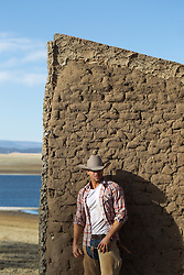 cowboy leaning up against an adobe wall on a ranch in New Mexico
