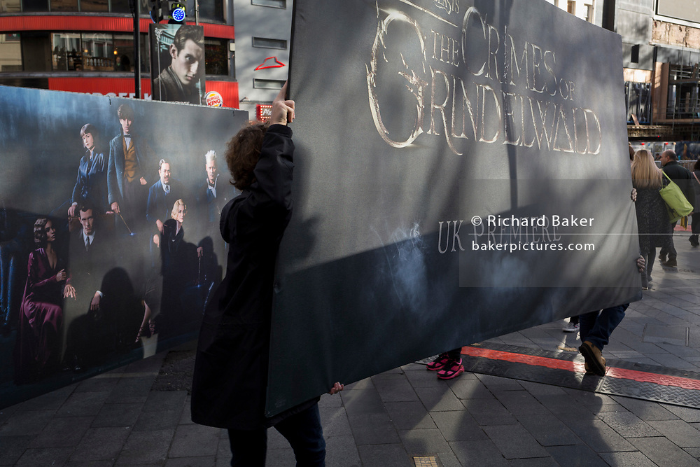 Contractors carry a publicity board for the new film 'Fantastic Beasts: The Crimes of Grindelwald', hours before its UK premier in Leicester Square, on 13th November 2018, in London, England.