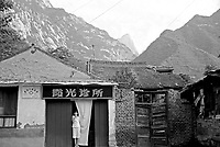 China, Xi'an, 2008. A young girl stands in the doorway of a neighborhood women's health clinic at the base of scenic Hua Shan mountain.