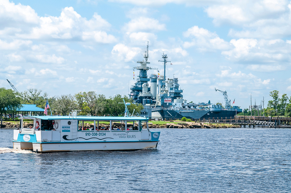 The Wilmington Water Tours pontoon boat cruises up the Cape Fear River in front of the Battleship North Carolina in Wilmington, North Carolina on Monday, August 9, 2021. Copyright 2021 Jason Barnette