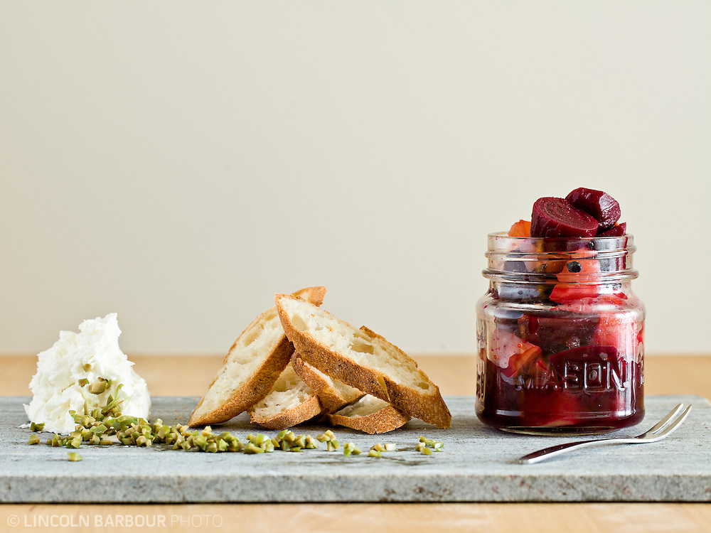 Goat Cheese with Capers, Pickled Beets, & Baguette on a marble slab